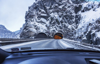 First person driver view through windshield of a car speeding toward the eastbound entrance to the US Interstate 70 Hanging Lake Tunnel which carries the expressway through parallel tunnels under the massive granite rock mountain wall of Glenwood Canyon, near Glenwood Springs, Colorado in the Rocky Mountains Range. Winter in early February, 2016.